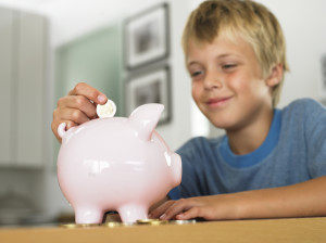 Child saving with piggy bank