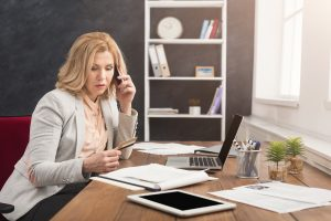Businesswoman at work talking on phone and shopping online